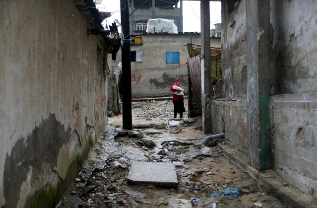 A Palestinian woman holds her child as she walks at Khan Younis refugee camp on a rainy day in the southern Gaza Strip February 22, 2016. (Photo by Ibraheem Abu Mustafa/Reuters)