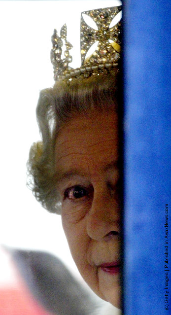 HRH Queen Elizabeth II peers around the side of her carriage as she leaves Parliament