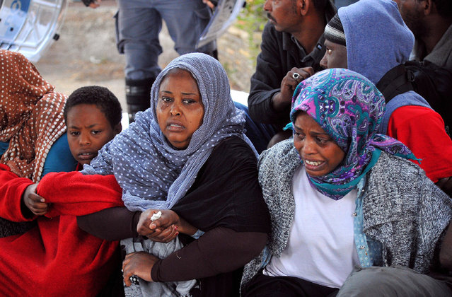 Two women cry as Italian Police remove migrants in Ventimiglia, at the Italian-French border Tuesday, June 16, 2015. Police at Italy's Mediterranean border with France have forcibly removed some of the African migrants who have been camping out for days in hopes of continuing their journeys farther north. The migrants, mostly from Sudan and Eritrea, have been camped out for five days after French border police refused to let them cross. (Luca Zennaro/ANSA via AP)