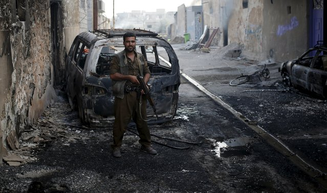 A Kurdish gunman stands in front of burned vehicle during clashes with Shi'ite militia in Tuz Khurmato, Iraq, April 24, 2016. (Photo by Goran Tomasevic/Reuters)