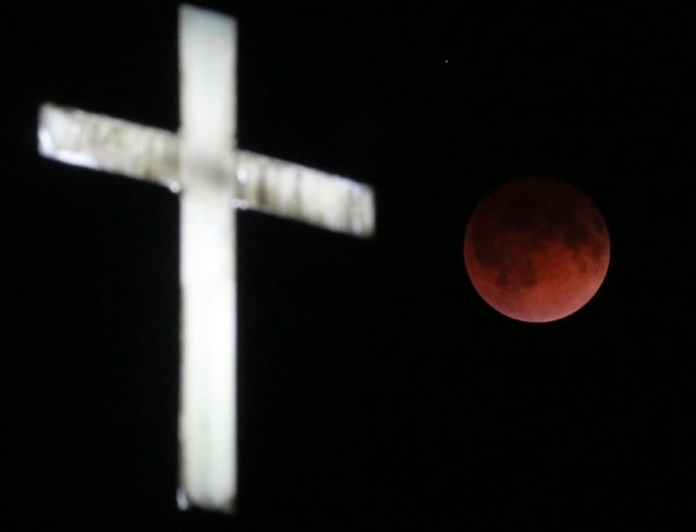 The Earth's shadow renders the moon in a crimson hue during a total lunar eclipse behind the illuminated steeple of St. Olaf Lutheran Church in the town of Ashippun , Wis. Tuesday, April 15, 2014. (Photo by John Hart/AP Photo/Wisconsin State Journal)