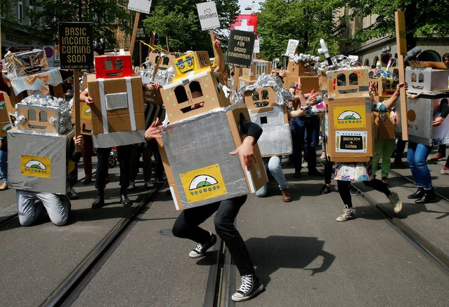 Protesters dressed as robots demand a basic income for everyone during a demonstration at the Bahnhofstrasse in Zurich, Switzerland April 30, 2016. (Photo by Arnd Wiegmann/Reuters)