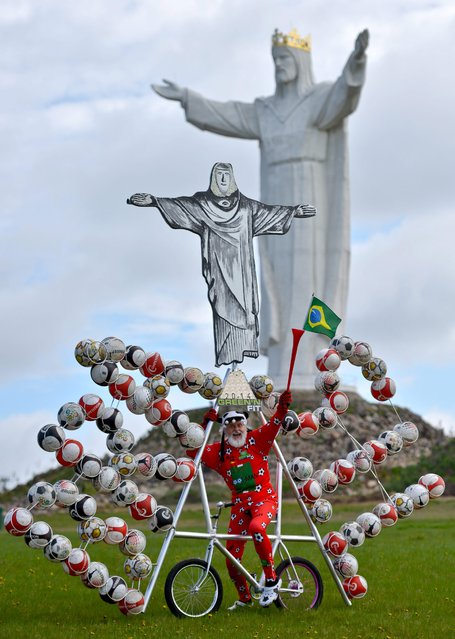 Bicycle designer Dieter 'Didi' Senft poses for photographs as he presents his soccer bicycle for the Soccer World Cup in Brazil in Swiebodzin, Poland, 15 April 2014. The designer from Brandenburg has designed a bicycle incorporating a copy of the statue Christ the Redeemer in Rio de Janeiro and 72 soccer balls. There is a statue of Jesus in Swiebodzin which is six metres higher than the one on Rio de Janeiro. (Photo by Patrick Pleul/EPA)