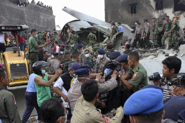 Security forces and rescue teams remove the bodies of victims from the wreckage of an Indonesian military C-130 Hercules transport plane after it crashed into a residential area in the North Sumatra city of Medan, Indonesia, June 30, 2015. (Photo by Irsan Mulyadi/Reuters/Antara Foto)