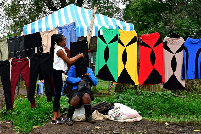 A woman plaits her friend's hair as they sell second-hand clothes in Nairobi's Makadara district, Kenya on June 06, 2019. (Photo by Simon Maina/AFP Photo)