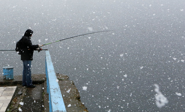 A man fishes on the bank of the Yenisei river during a snowfall in the Siberian town of Divnogorsk, Russia, May 2, 2016. (Photo by Ilya Naymushin/Reuters)