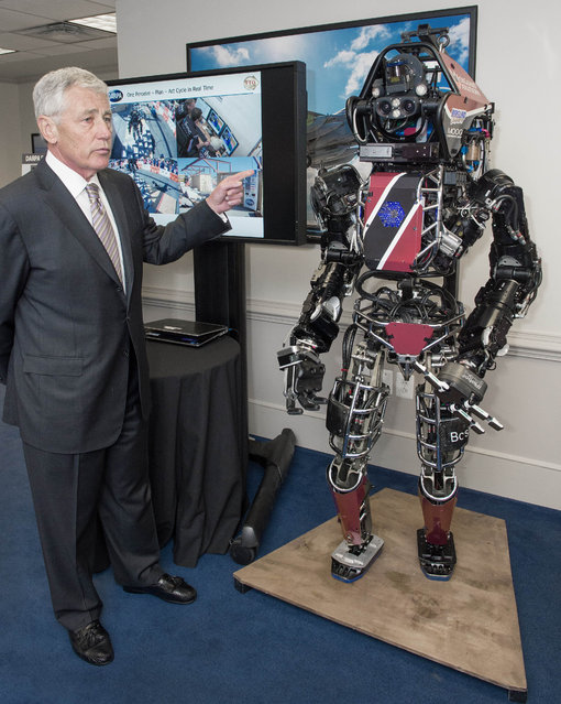 US Secretary of Defense Chuck Hagel is briefed on the Atlas Robot which is one of the most advanced humanoid robots ever built April 22, 2014, at the Pentagon by Defense Advanced Research Projects Agency (DARPA) personnel demonstrating five technologies under development. The six-foot-two, 330-pound Atlas is capable of a range of natural movements and is equipped with an on-board real-time control computer, hydraulic pump and thermal management. (Photo by Paul J. Richards/AFP Photo)