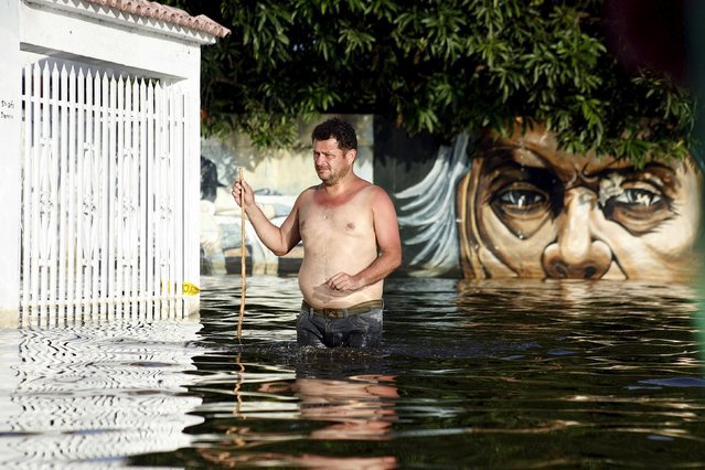 A man walks in a flooded street in Guasdualito, in the state of Apure, Venezuela, July 4, 2015. (Photo by Carlos Eduardo Ramirez/Reuters)