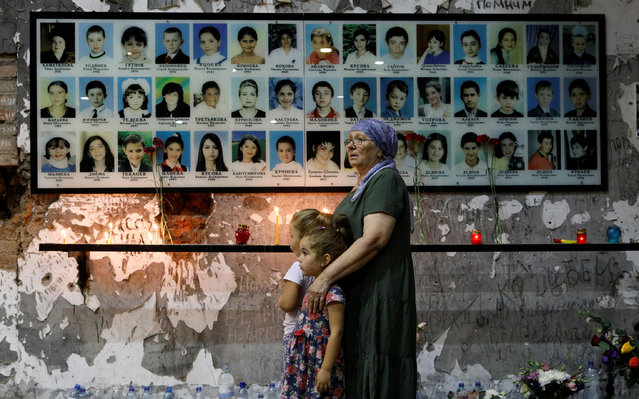 A woman with two young girls is seen in front of the photographers of victims, as people gather in the gym of a school, the scene of the hostage crisis, in memory of victims on the fifteenth anniversary of the tragedy in Beslan, North Ossetia region this Sunday, September 1, 2019. More than 330 people, including 186 children, died as a result of the terrorist attack at the school on Sept. 1, 2004 in Beslan. (Photo by Eduard Korniyenko/Reuters)