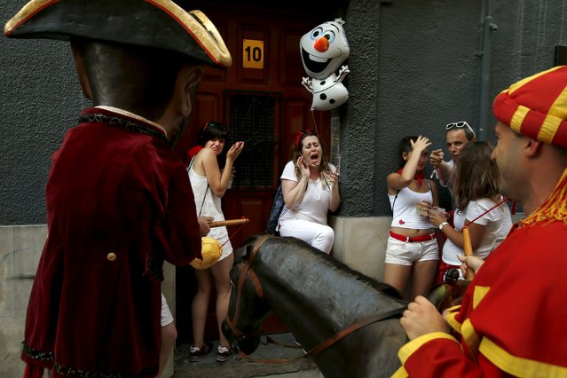 """Women react before being hit with a sponge by a Kiliki (L) during San Fermin festival's """"Comparsa de gigantes y cabezudos"""" (Parade of Giants and Big Heads) in Pamplona, northern Spain, July 6, 2015. """"Kilikis"""", wearing oversized masks as they playfully hit bystanders with sponges on sticks, parade daily through the city accompanied by brass bands during the nine-day-long festival made popular by U.S. writer Ernest Hemingway. (Photo by Susana Vera/Reuters)"""