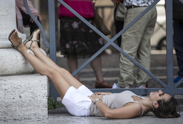 A woman lays on the ground during a hot day in Rome, Italy, 07 July 2015. Temperatures of around 33 degrees were forecast in Rome as various European countries experienced a heat wave. (Photo by Massimo Percossi/EPA)
