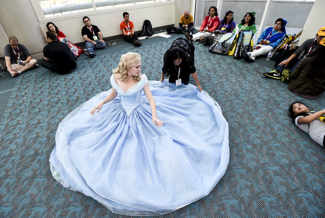 Carissa Ohm, dressed as Cinderella, takes a break as Annie Huynh adjusts her dress on the second day of the 2015 Comic-Con International held at the San Diego Convention Center Friday, July 10, 2015, in San Diego.  (Photo by Denis Poroy/Invision/AP Photo)