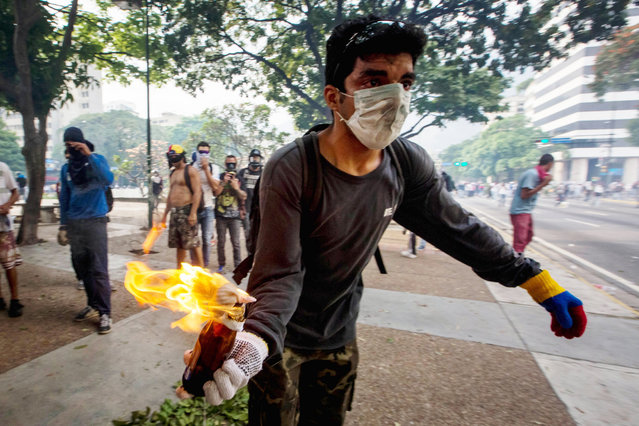 A demonstrators holds a Molotov cocktail during clashes with police during protests in Caracas, Venezuela, 19 April 2017. Police, using tear gas, dispersed protesters in the center of Caracas. Venezuela is the scene of massive protests for both government supporters and opposition groups heightening tension throughout the country. (Photo by Miguel Gutierrez/EPA)