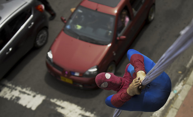 """Colombian Jahn Fredy Duque, dressed as superhero """"Spiderman"""", performs on the streets in Bogota, Colombia on April 24, 2017. (Photo by Raul Arboleda/AFP Photo)"""