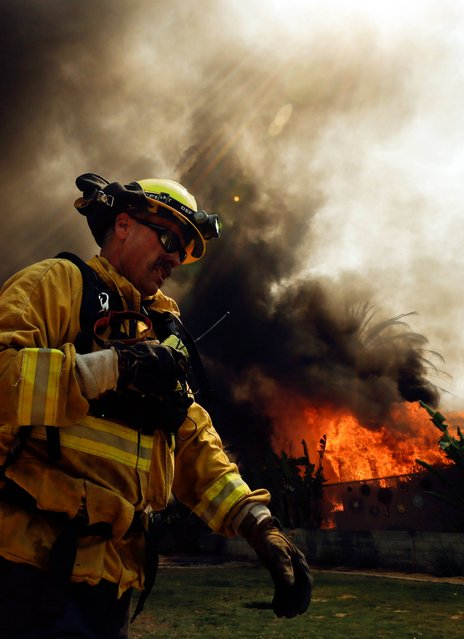 A firefighter moves past a burning structure during a wildfire Thursday, May 15, 2014, in Escondido, Calif. One of the nine fires burning in San Diego County suddenly flared Thursday afternoon and burned close to homes, trigging thousands of new evacuation orders. (Photo by Gregory Bull/AP Photo)