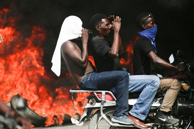 Protesters ride a motorbike during a demonstration to demand the resignation of Haitian president Jovenel Moise, in the streets of Port-au-Prince, Haiti on October 4, 2019. (Photo by Andres Martinez Casares/Reuters)