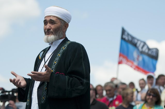 A Muslim clergyman attends a memorial ceremony at the crash site of the Malaysian Airlines MH17 plane near the village of Hrabove, eastern Ukraine, Friday, July 17, 2015. (Photo by Antoine E. R. Delaunay/AP Photo)