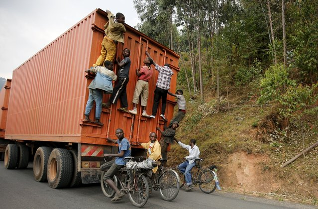 Cylists hang to the back of a truck outside the capital Bujumbura, July 19, 2015, as the country awaits next week's presidential elections. Each day scores of cyclists make the 45 kilometer downhill journey at breakneck speed from Bugarama to sell bananas, often hanging from the back of trucks for the return uphill trip. (Photo by Mike Hutchings/Reuters)
