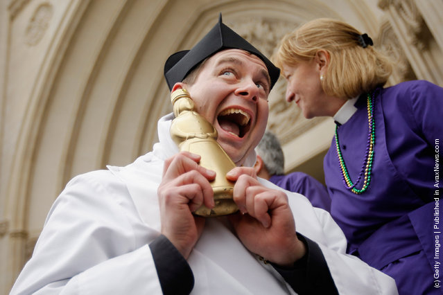 Father Matthew Hanisian, assistant rector at St. Alban's Parish, poses with his gold-painted syrup bottle trophy after winning a pancake race during the Shrove Tuesday, or Mardi Gras, tradition at the National Cathedral