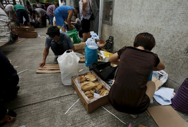 People handle frozen beef tripe from Brazil on a back street at an industrial area in Hong Kong before they are smuggled across the border into mainland China, July 8, 2015. (Photo by Bobby Yip/Reuters)