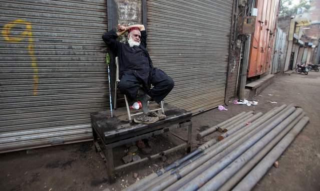 A worker sits outside closed shops during a country-wide lock down by the traders and business community, against what they say is imposition of taxes by the government in Lahore, Pakistan on October 29, 2019. (Photo by Mohsin Raza/Reuters)