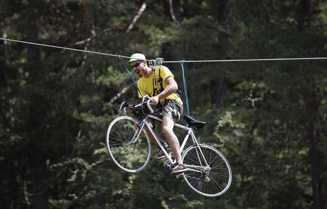 A fan rides a bicycle as he is suspended from a cable during the 161-km (100 miles) 17th stage of the 102nd Tour de France cycling race from Digne-les-Bains to Pra Loup in the French Alps mountains, France, July 22, 2015. (Photo by Stefano Rellandini/Reuters)