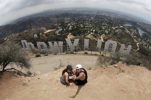 A couple poses for a selfie behind the Hollywood sign in Los Angeles, California, United States July 9, 2015. (Photo by Lucy Nicholson/Reuters)