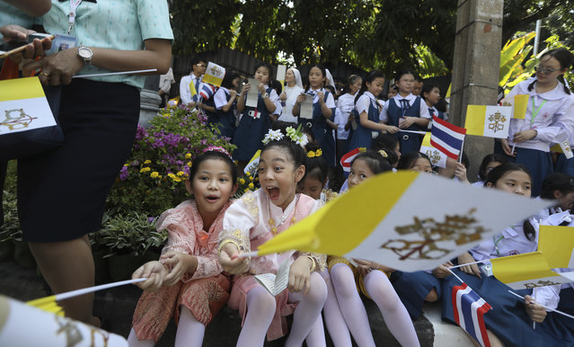 School children wait for the arrival Pope Francis outside Apostolic Nunciature Embassy of the Holy See in Bangkok, Thailand, Wednesday, November 20, 2019. Pope Francis arrived in Bangkok on Wednesday to begin a tour of Thailand and Japan, part of a mission to boost the morale of those countries' tiny minority Catholic communities and speak about issues of concern including human trafficking and peacemaking. (Photo by Manish Swarup/AP Photo)