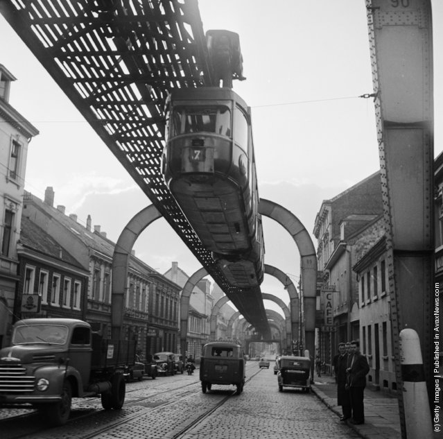 1956:  A hanging monorail train moves along the seven mile Wuppertal Monorail System in Germany, just above the stream of traffic