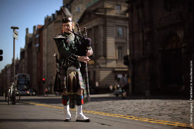 A piper plays on the Royal Mile