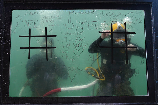 Divers are pictured waiting to play tic-tac-toe on the glass of a dive tank used by the U. S. Navy Mobile Diving and Salvage Unit for promotion during Fleet Week in Times Square in the Manhattan borough of New York, U.S., May 27, 2016. (Photo by Carlo Allegri/Reuters)