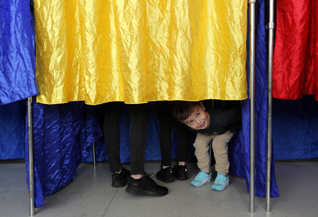 A Romanian kid stare out of the voting booth while waiting for his mother to stamp her ballot at 'Cezar Bolliac' polling station during the first round of presidential elections in Bucharest, Romania, 10 November 2019. Romanians are voting today for the first round of the presidential elections. (Photo by Robert Ghement/EPA/EFE)