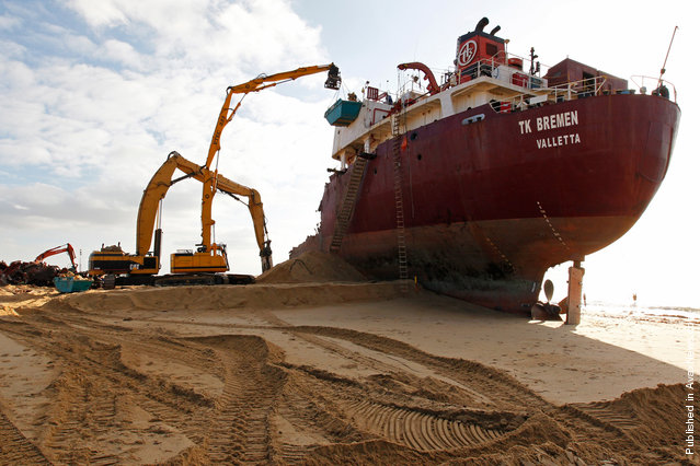 Workers tear apart the grounded TK Bremen, on January 13, 2012