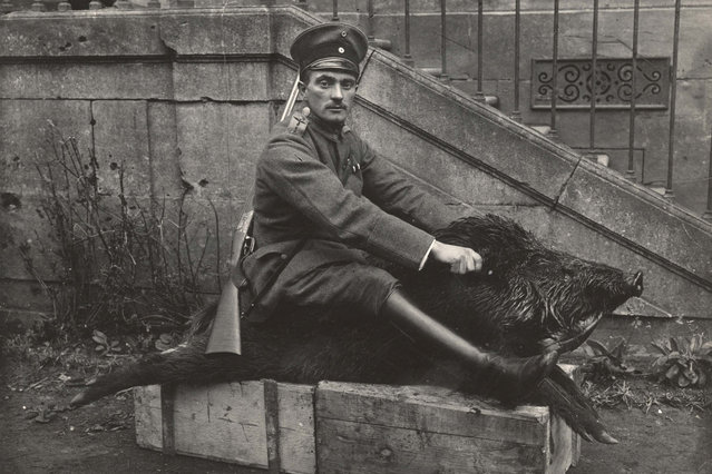 A German Air Force Officer sits astride a dead boar outside a house where he is stationed near the Western Front, in this 1918 handout picture. This picture is part of a previously unpublished set of World War One (WWI) images from a private collection. The pictures offer an unusual view of varied and contrasting aspects of the conflict, from high tech artillery to mobile pigeon lofts, and from officers partying in their headquarters to the grim reality of life and death in the trenches. The year 2014 marks the centenary of the start of the war. (Photo by Reuters/Archive of Modern Conflict London)