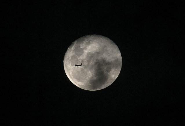 A general view shows a plane flying in front of the full moon over Rio de Janeiro, Brazil, 05 May 2015. (Photo by Marcelo Sayao/EPA)