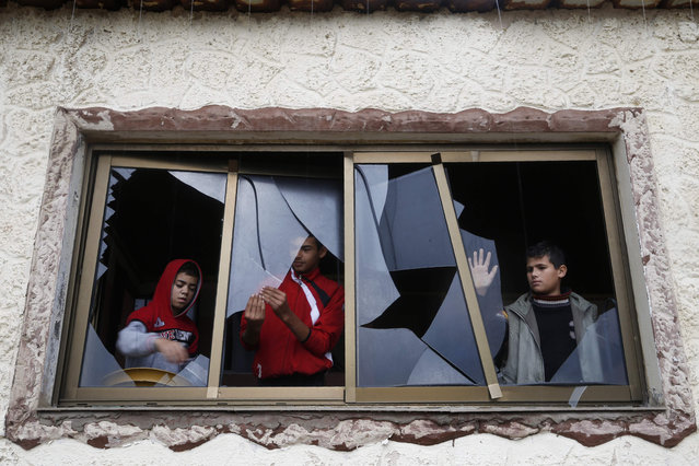 Palestinian boys pull shards of glass from a broken window at their home near the site of Israeli overnight attacks in Gaza City on December 8, 2019. Israeli aircrafts carried out attacks in the Hamas-controlled Gaza Strip early today, hours after militants in the enclave launched three rockets at the Jewish state. The strikes targeted two sites belonging to Al-Qassam Brigades, the Hamas military wing, in northern Gaza, with another series of sorties at a Qassam site west of Gaza City, Hamas officials said. (Photo by Mohammed Abed/AFP Photo)