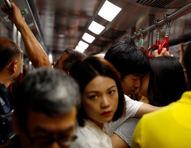 A couple shares a light moment in a Mass Transit Railway (MTR) subway train in Hong Kong, China on August 28, 2019. (Photo by Anushree Fadnavis/Reuters)