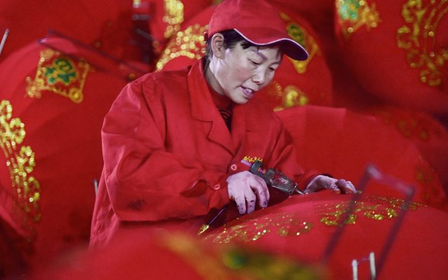 A worker makes red lanterns ahead of upcoming Lunar New Year celebrations on January 25, 2020, at a factory in Wuyi in China's eastern Zhejiang province on December 26, 2019. (Photo by AFP Photo/China Stringer Network)
