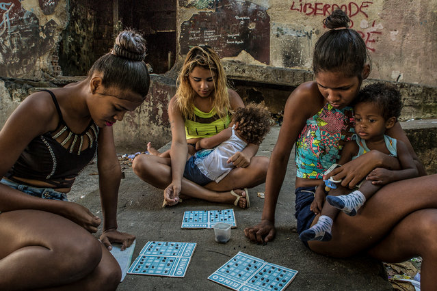 Mothers aged between 16 and 18 play bingo using black beans as chips. (Photo by Tariq Zaidi/The Guardian)