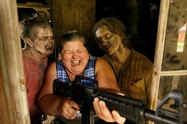 """Tourist Amy Powers is approached by """"Walker"""" Matthew Tomlin during The Walking Dead Tour of a Season 3 location of the AMC production in Haralson, Georgia, U.S. on June 15, 2019. (Photo by Chris Aluka Berry/Reuters)"""