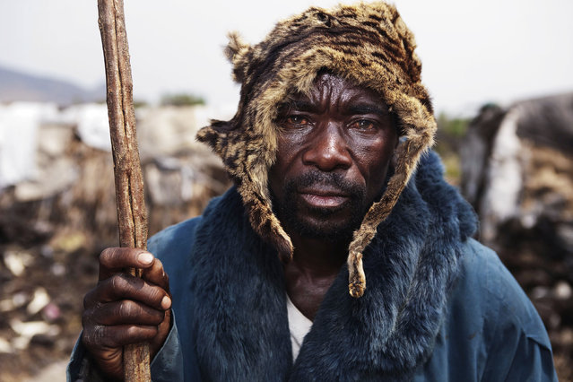 Nzamburba, 57, who is a member of a pygmy community, wears the skin of a wild cat on his head at Mugunga, just west of the eastern Congolese city of Goma, August 24, 2010. (Photo by Finbarr O'Reilly/Reuters)