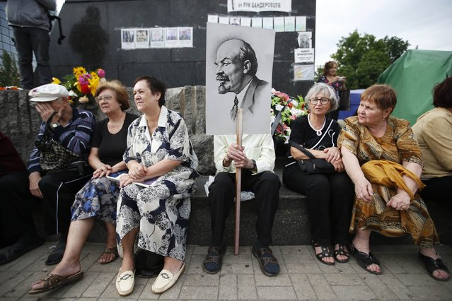Participants sit beneath a statue of Lenin during a protest against Ukrainian military action held in the centre of the eastern Ukrainian city of Donetsk July 6, 2014. Ukraine's government said it would quickly seize more territory from rebels after re-taking the separatist stronghold of Slaviansk in what President Petro Poroshenko called a turning point in the fight for control of the country's east. (Photo by Maxim Zmeyev/Reuters)