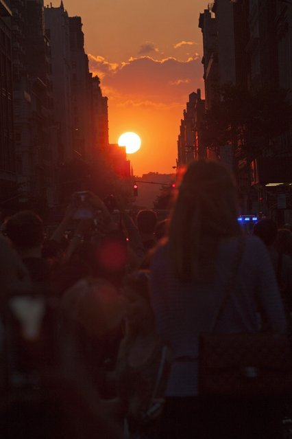 """People watch the sunset during the bi-annual occurrence """"Manhattanhenge"""" in New York July 11, 2014. Manhattanhenge, coined by astrophysicist Neil deGrasse Tyson, occurs when the setting sun aligns itself with the east-west grid of streets in Manhattan, allowing the sun to shine down all streets at the same time. (Photo by Eduardo Munoz/Reuters)"""