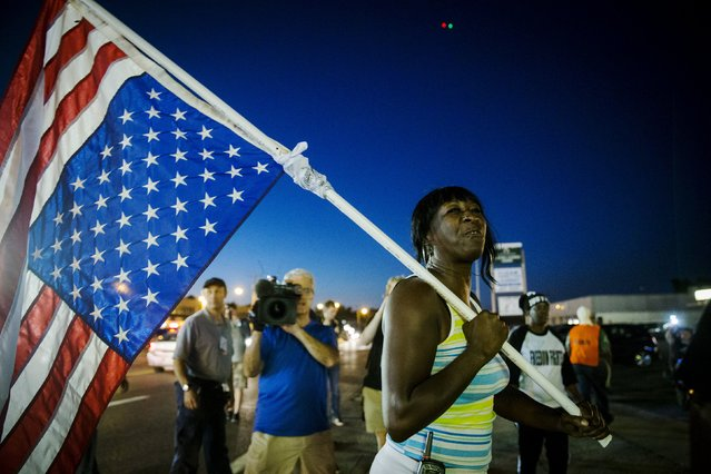 An anti-police demonstrator marches in protest in Ferguson, Missouri August 10, 2015. Police in riot gear clashed with protesters who had gathered in the streets of Ferguson early on Tuesday to mark the anniversary of the police shooting of an unarmed black teen whose death sparked a national outcry over race relations. (Photo by Lucas Jackson/Reuters)