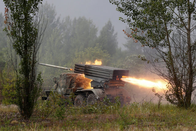 A Grad multiple rocket launcher system fires during a military exercise for Ukrainian army reservists at a shooting range near the village of Goncharivske in Chernihiv region, Ukraine, June 22, 2016. (Photo by Valentyn Ogirenko/Reuters)