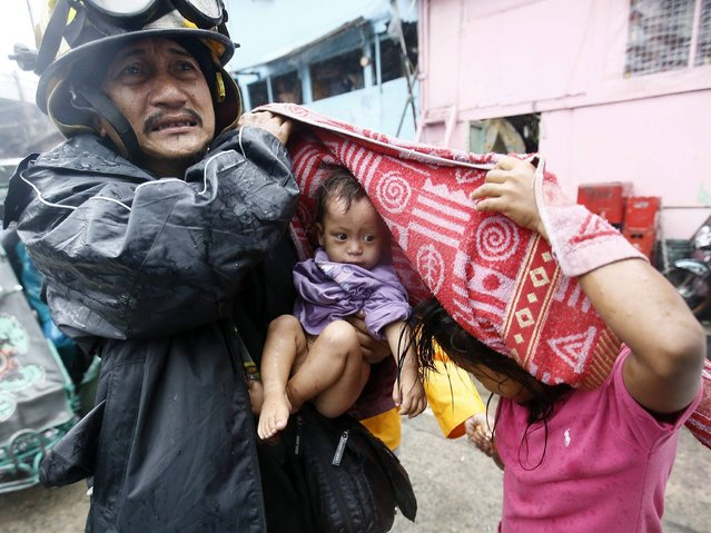 A Filipino rescue worker carries a child after an evacuation was implemented due to Typhoon Rammasun in Manila, Philippines, 16 July 2014. (Photo by Dennis M. Sabangan/EPA)