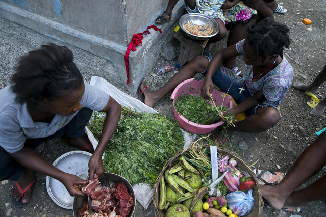 In this December 3, 2019 photo, street vendors ready ingredients to make soup to sell in the Cite Soleil slum of Port-au-Prince, Haiti. Disruption caused by recent protests, combined with rising commodity prices and the depreciation of the Haitian gourde against the US dollar, has reduced the ability of Haiti's poorest to buy food. (Photo by Dieu Nalio Chery/AP Photo)