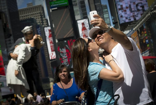 """A couple takes a """"selfie"""" photo near a replica sculpture of the famous photo by Alfred Eisenstaedt in New York's Times Square August 13, 2015. The replica is being displayed to celebrate the 70th anniversary of the iconic photograph of the most famous kiss in American history that was captured between an American sailor and nurse on August 14, 1945, marking the end of World War Two. (Photo by Brendan McDermid/Reuters)"""