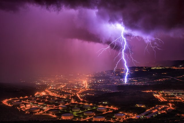 There may be a heatwave in the UK, but other parts of Europe have been hit by massive thunderstorms. Electric lightning bolts illuminated the stormy skies of Italy, cracking through the clouds to strike the ground below. (Photo by Marko Korosec/Solent News & Photo Agency)