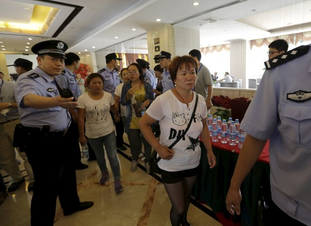 Relatives of missing firefighters are guided by policemen outside the venue of a news conference as they try to demand for more information from government officials, following explosions on Wednesday night at Binhai new district in Tianjin, China, August 15, 2015. (Photo by Jason Lee/Reuters)